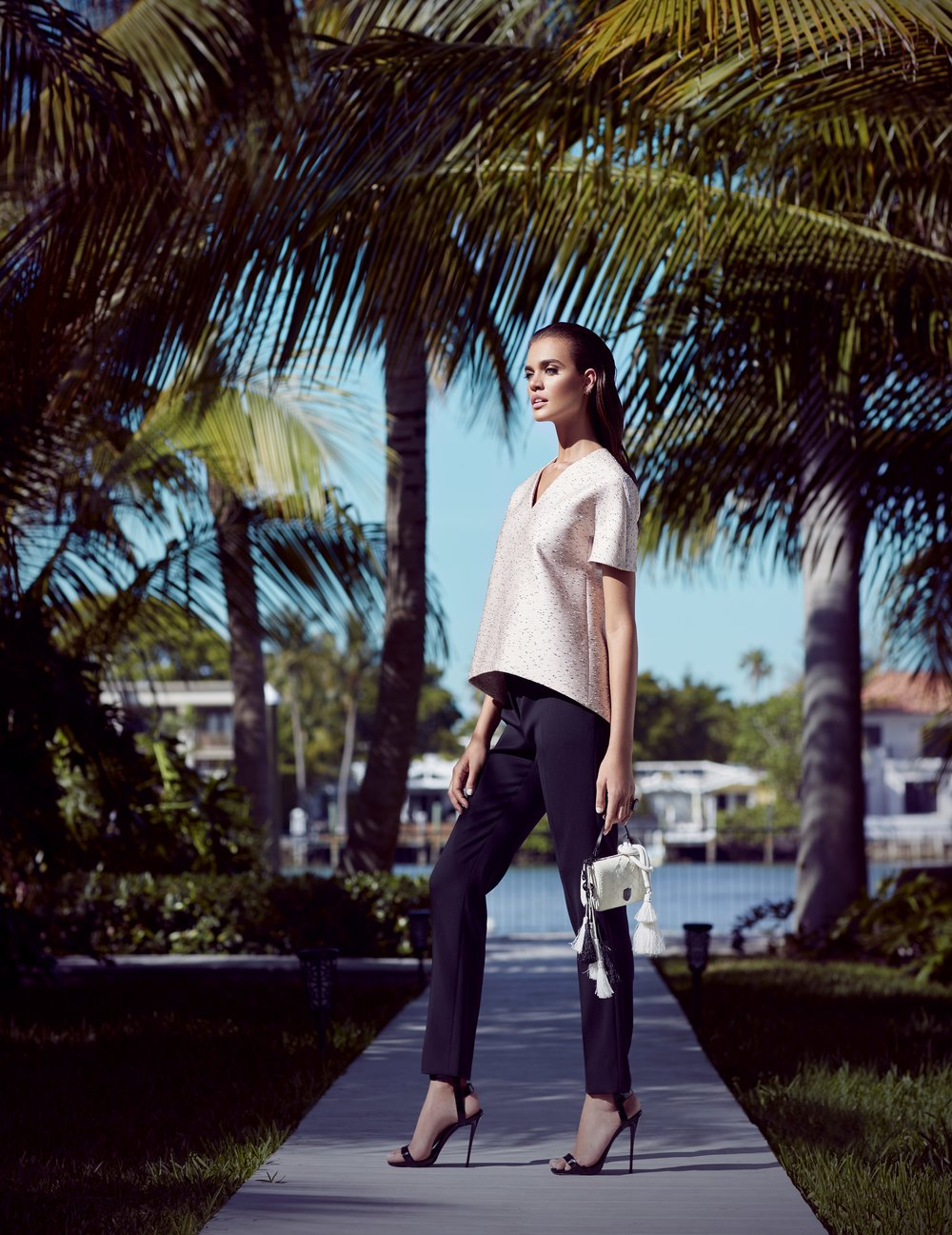 Brunette woman wearing off-white top with dark pants and high heels holding a small white purse standing on the sidewalk in a beachfront community - Mark DeLong: Fashion Gallery