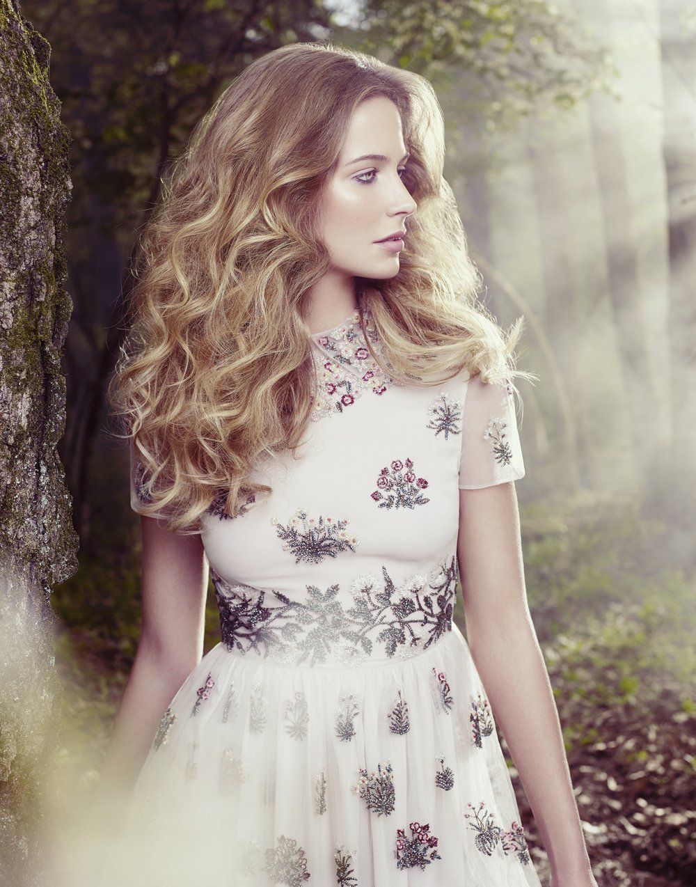 Blonde woman wearing white dress with floral rose and daisy design looking to the side in a meadow - Mark DeLong: Fashion Gallery