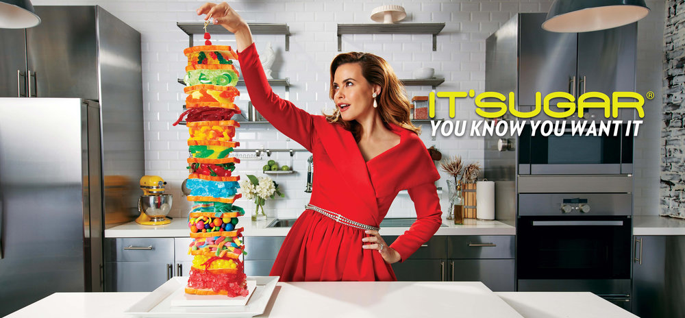 Mark DeLong - Commercial Photography - Woman in red dress stacks food in kitchen.