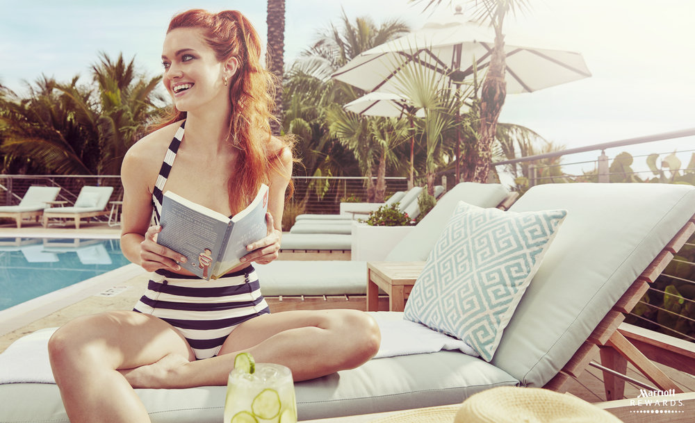 Mark DeLong - Commercial Photography - Girl in a blue and white striped swim suit sits next to a pool and holds a book.