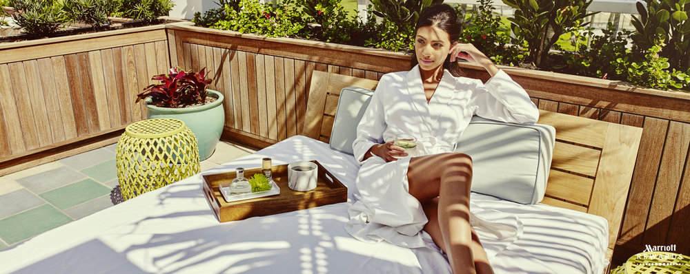 Mark DeLong - Commercial Photography - Woman in white dress sits on outdoor bed.