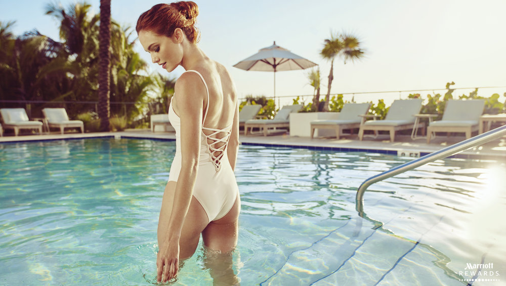 Mark DeLong - Commercial Photography - Woman in a white swimsuit stands thigh deep in a pool.