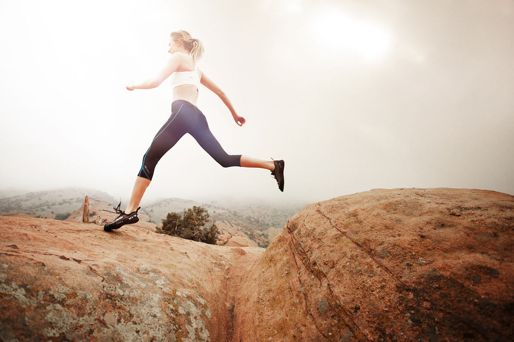 Mark DeLong - Lifestyle Photography - A woman jumping across rocks in athletic wear