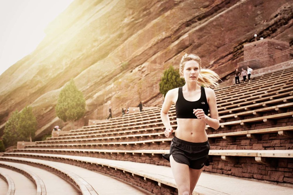 Mark DeLong - Lifestyle Photography - A woman running in an outdoor amphitheater in a sports bra and athletic shorts