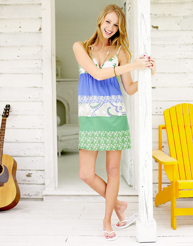 Mark DeLong - Lifestyle Photography - A girl in a blue and green dress leaning against a pole on a front porch with a yellow chair and guitar