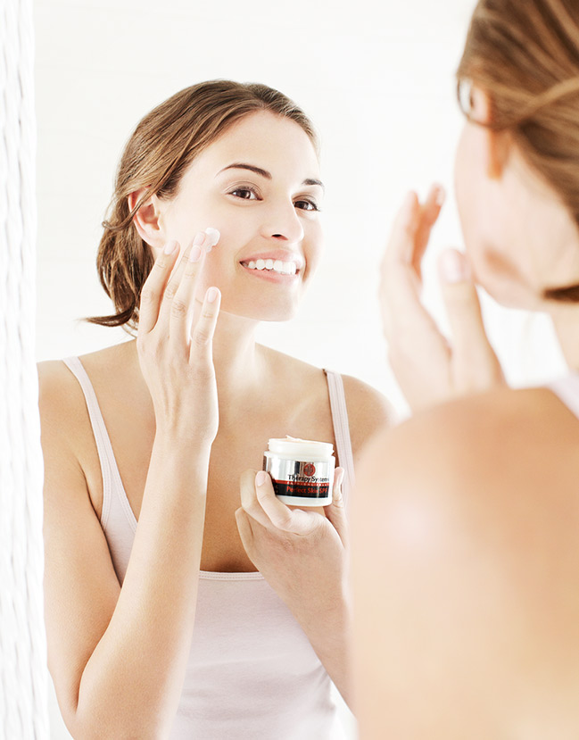 Mark DeLong - Lifestyle Photography - A brunette woman looking into a mirror applying face cream