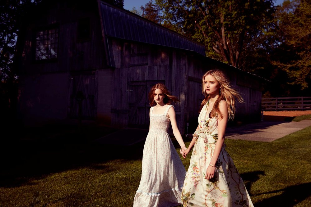 Two girls holding hands walking in front of old barn - Mark DeLong: Fashion Gallery