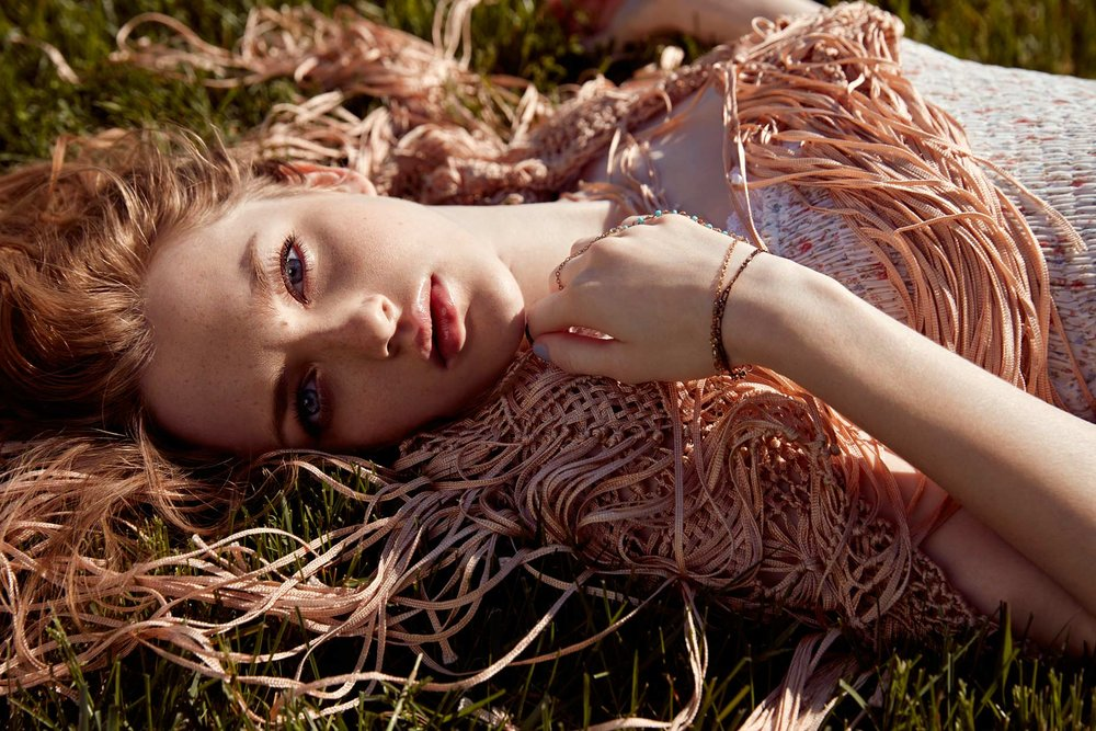 Woman with blue eyes and dirty blond hair laying in the grass - Mark DeLong: Fashion Gallery