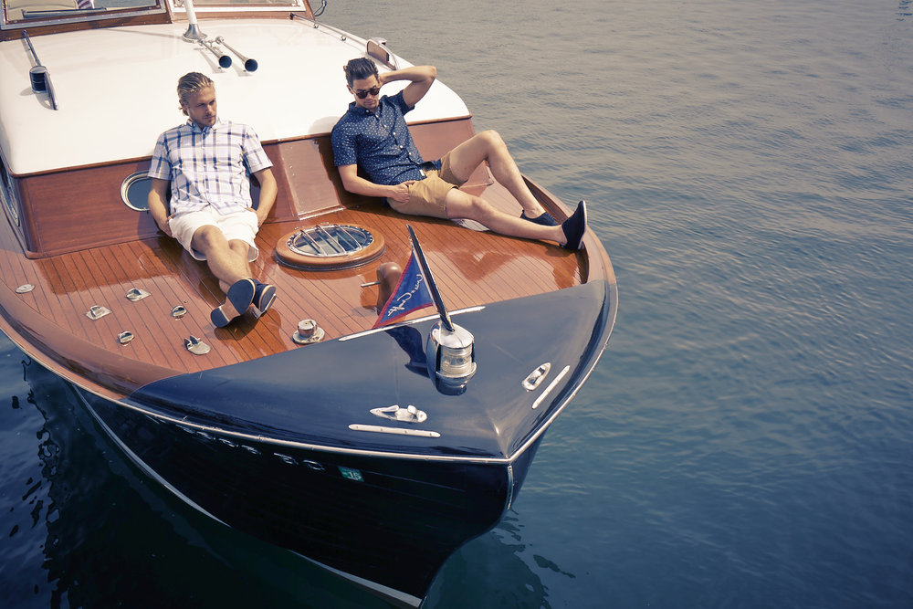 Mark DeLong - Lifestyle Photography - Two men lounging on the front of a cris craft boat in the ocean