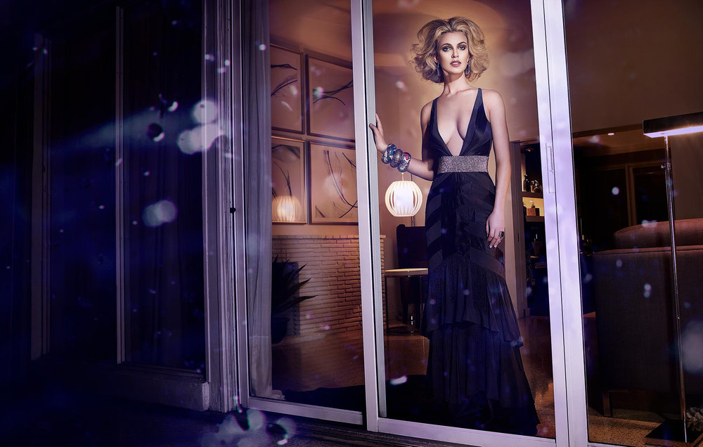 Woman with natural dirty blond hair wearing a dark long dress looking through a glass window- Mark DeLong: Fashion Gallery