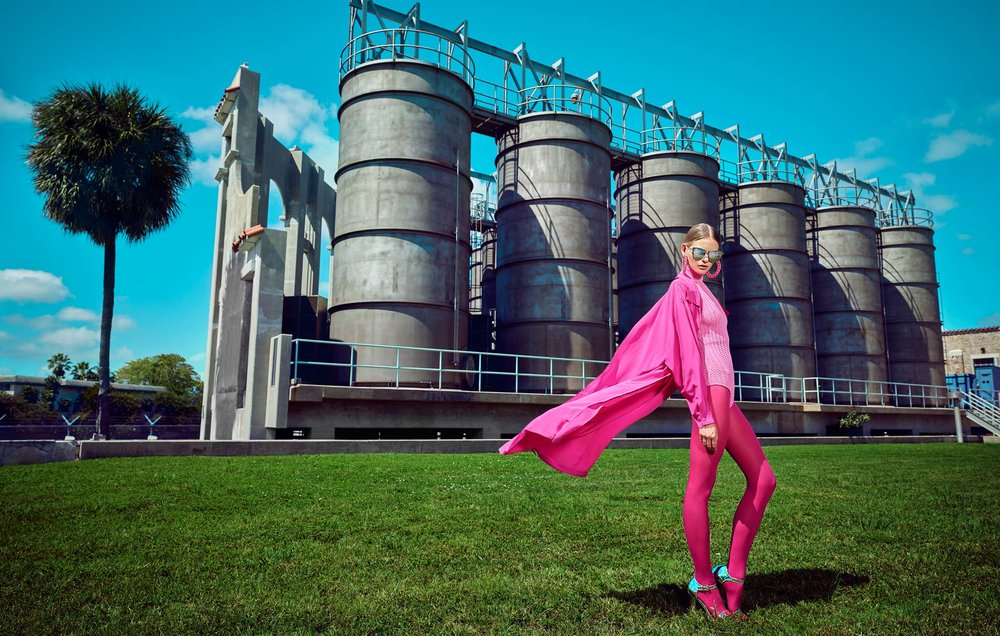 Posing woman wearing all pink outfit with pink cape flowing in the wind near large industrial storage tanks - Mark DeLong: Fashion Gallery