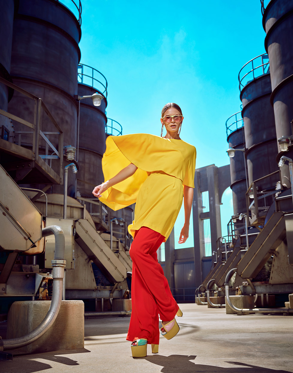 Woman walking with high heels, bright red pants and flowing yellow top in an industrial setting - Mark DeLong: Fashion Gallery