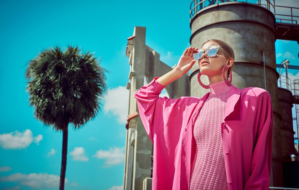 Woman with large mirrored sunglasses looking up to the sky wearing all pink turtle neck outfit with palm tree and sky in background - Mark DeLong: Fashion Gallery
