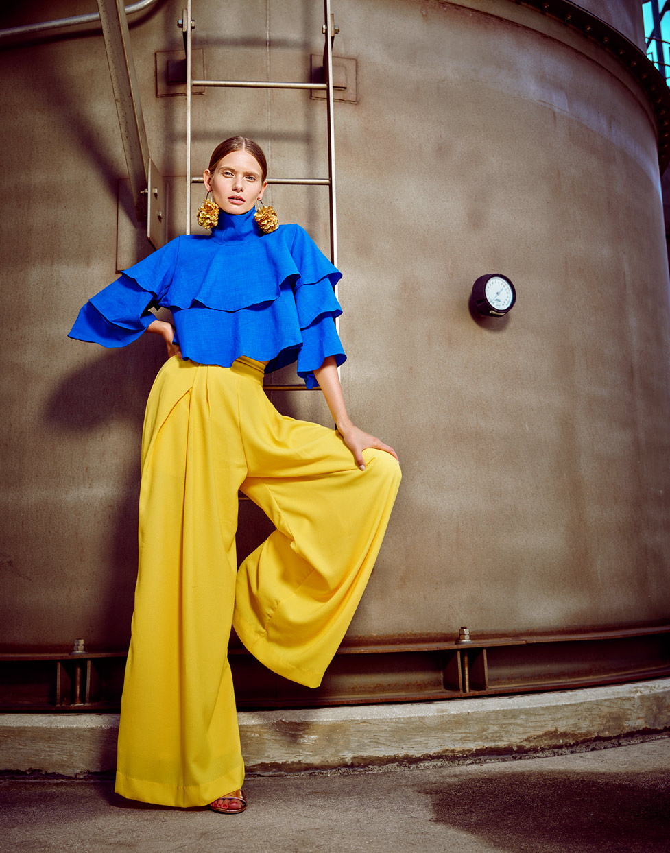 Woman modeling with bold blue top and bright yellow pants and earrings in front of metal storage tank - Mark DeLong: Fashion Gallery
