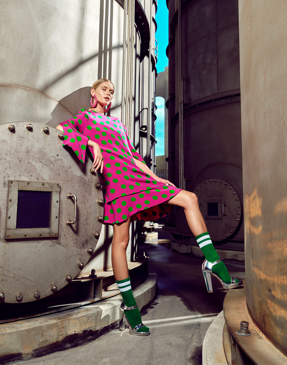 Woman with pink dress with green polka dots and high green socks leaning against metal industrial storage tank - Mark DeLong: Fashion Gallery