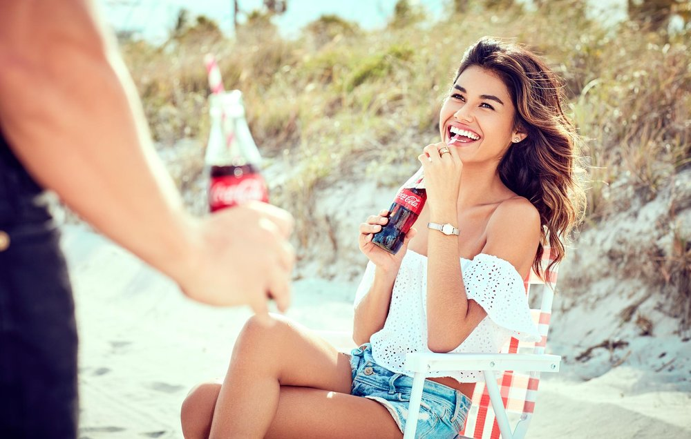 Mark DeLong - Lifestyle Photography - Woman sitting in a lawn chair laughing and looking up at a man drinking a coke
