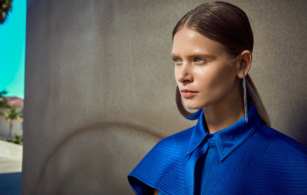 Focused woman staring into the distance with blue collar top and large silver hoop earrings - Mark DeLong: Fashion Gallery
