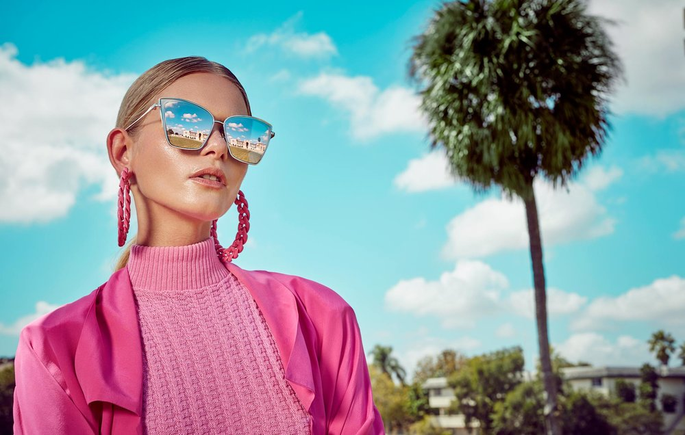 Scenic woman posing in pink turtle neck top with large pink hoop earrings and mirror sunglasses: Clouds and palm tree in the background- Mark DeLong: Fashion Gallery