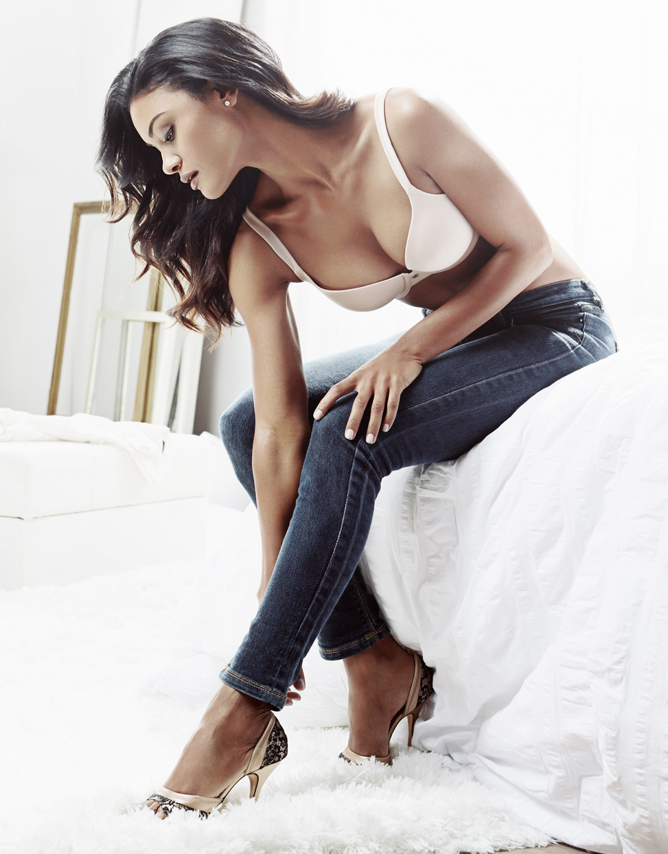 Mark DeLong - Beauty Photographer - Brunette woman wearing cream colored bra and long blue denim jeans putting on her gold high heels