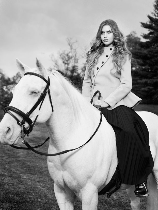 Black and white portrait of woman with long hair wearing stylish coat sitting on a white horse - Mark DeLong: Fashion Gallery