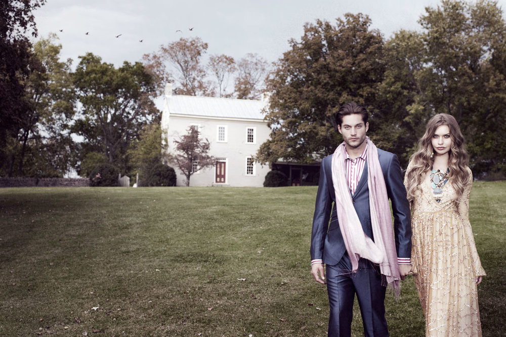 Man in navy suit with pink scarf walking with woman in tan long dress in front of home - Mark DeLong: Fashion Gallery