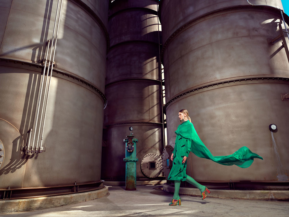 Woman wearing all green outfit with brown heels walking in front of industrial storage tanks - Mark DeLong: Fashion Gallery