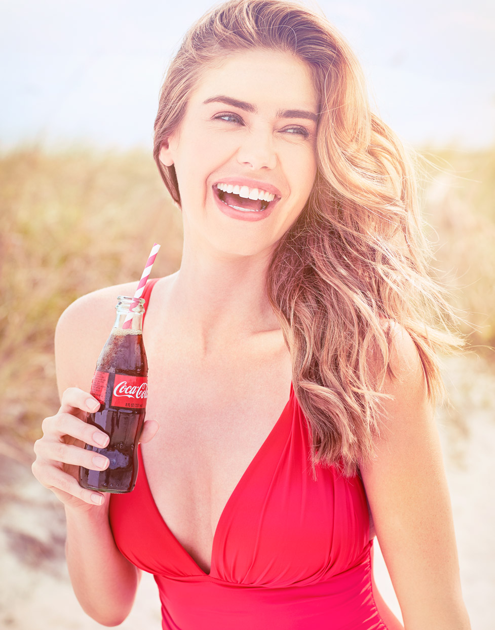 Mark DeLong - Lifestyle Photography - Woman in a red bathing suit laughing and drinking a soda
