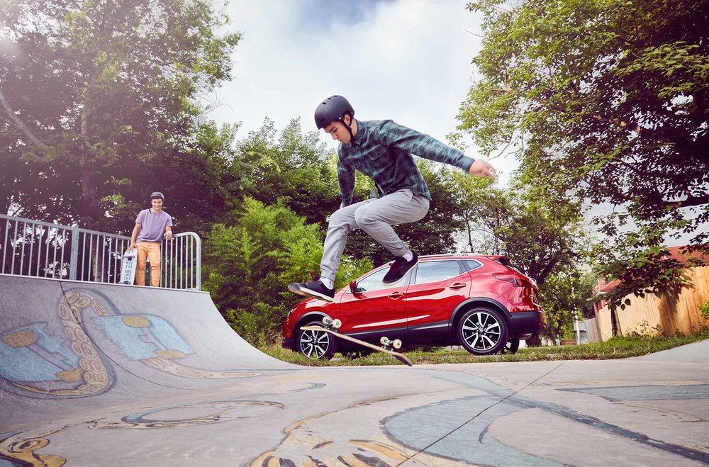 Mark DeLong - Commercial Photography - Young man does a kick flip with his skateboard in front of a red SUV.