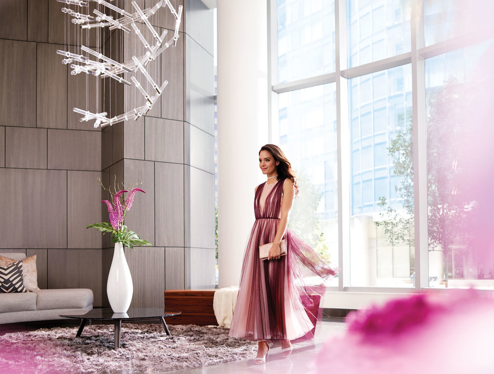 Mark DeLong - Commercial Photography - Woman in a pink dress in a large modern living room with pink accents.