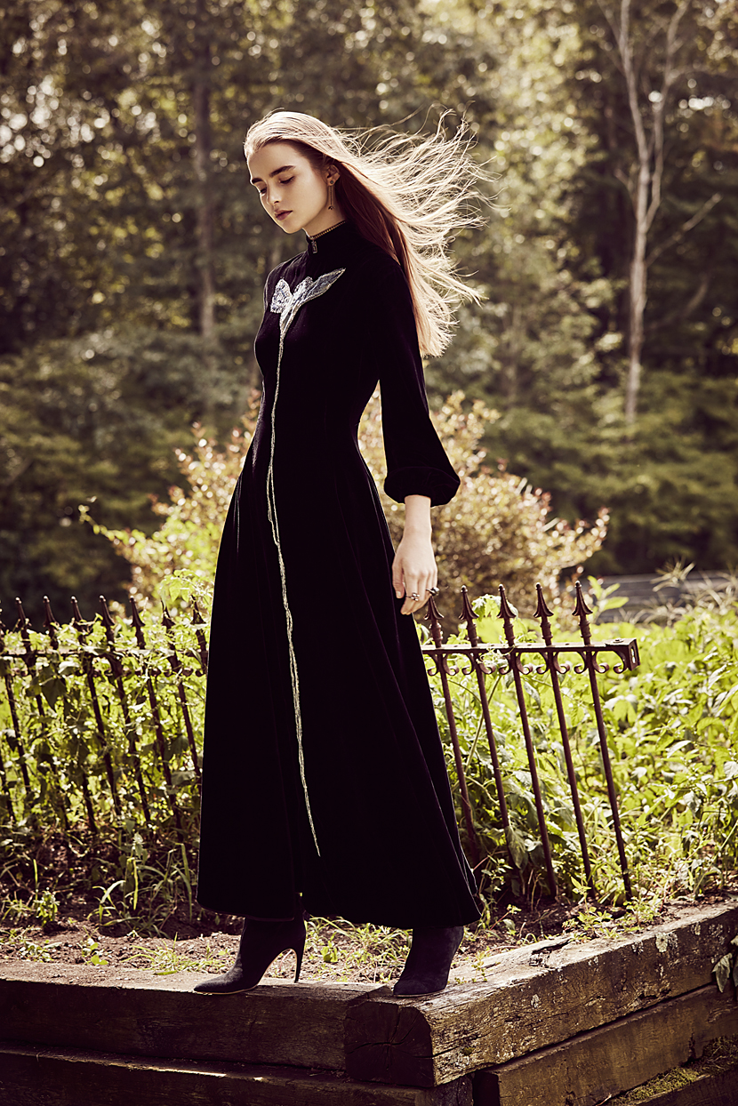 Brunette woman in all black long dress standing on wooden ledge - Mark DeLong: Fashion Gallery