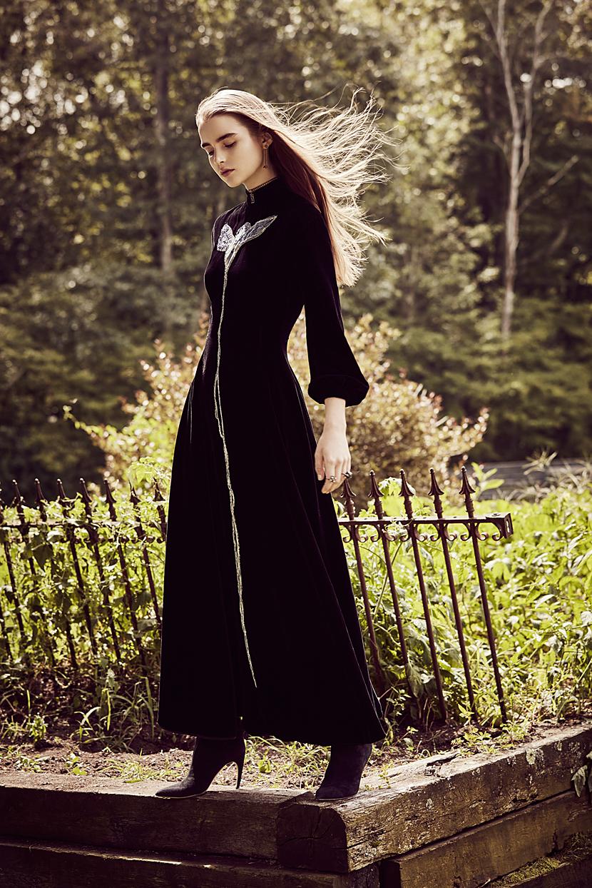 Brunette woman in all black long dress standing on wooden ledge - Mark DeLong: Fashion Gallery