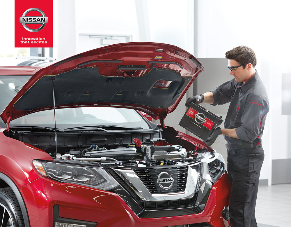 Mark DeLong - Commercial Photography - Man replaces battery to a red Nissan car.