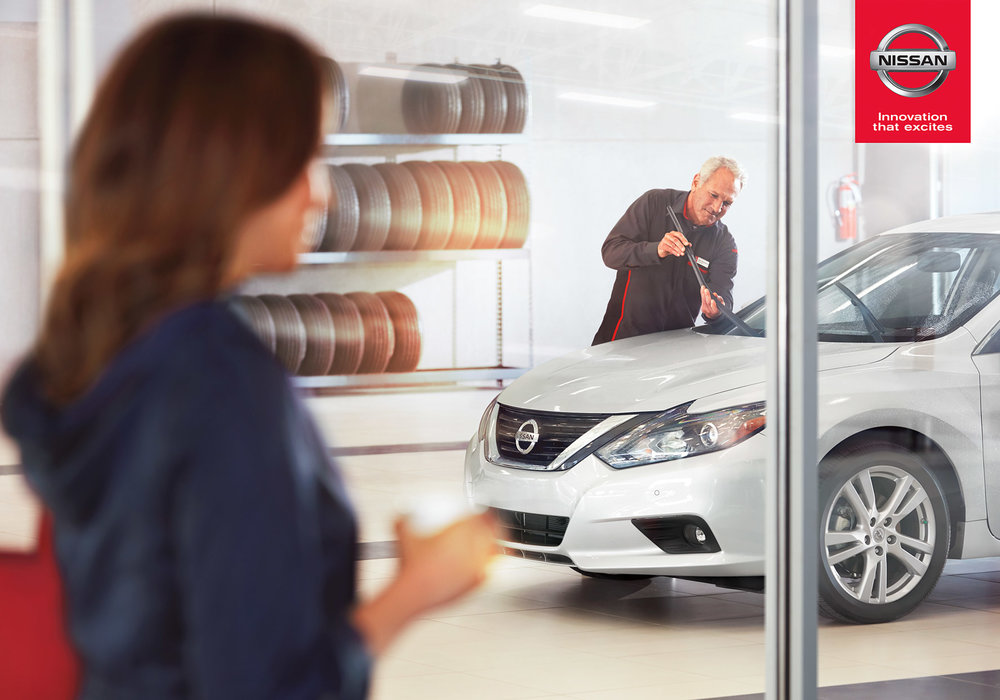 Mark DeLong - Commercial Photography - Older man replaces windshield wipers on a silver Nissan in a show room.