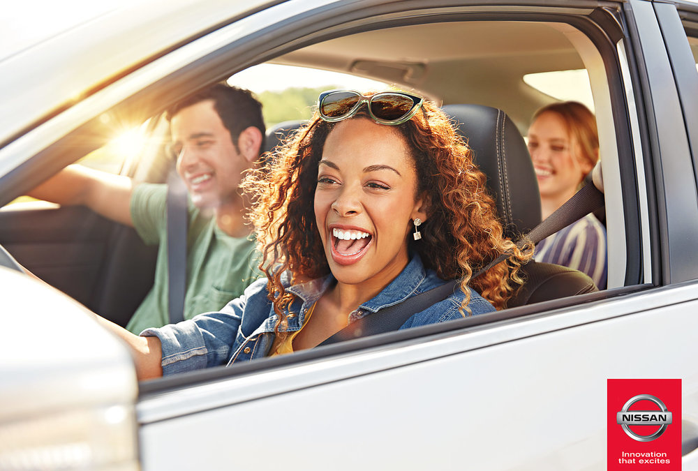 Mark DeLong - Commercial Photography - Three young adults smile as they drive a white Nissan car.