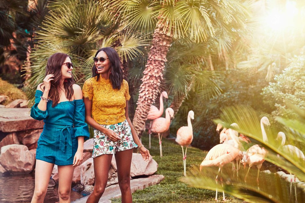 Mark DeLong - Commercial Photography - Woman in blue dress leans against woman in yellow outside near plastic flamingos.