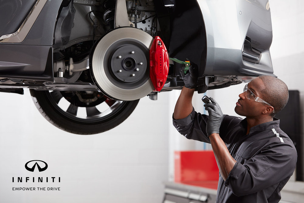 Mark DeLong - Commercial Photography - Mechanic inspects red brake pads of a silver vehicle that is raised to eye level.
