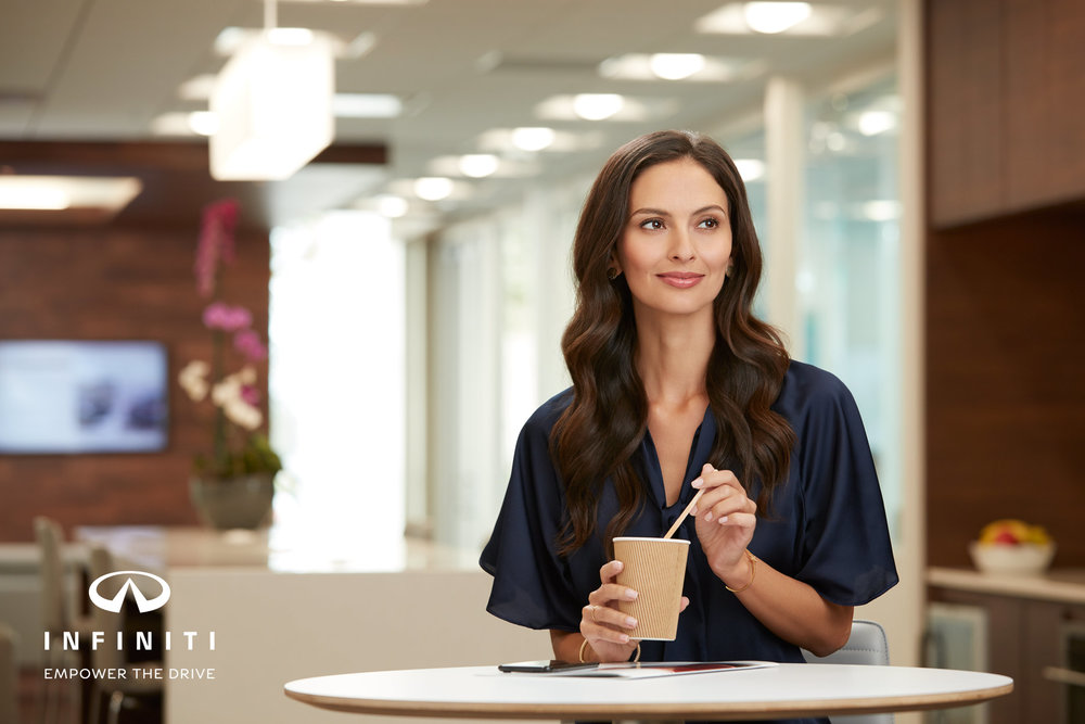 Mark DeLong - Commercial Photography - Woman in blue blouse sitting and stirring a coffee smiles as she looks to the right.