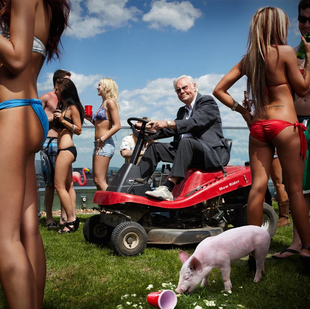 Mark DeLong - Celebrity Photographer - Celebrity riding lawn mower surrounded by women in bikinis.