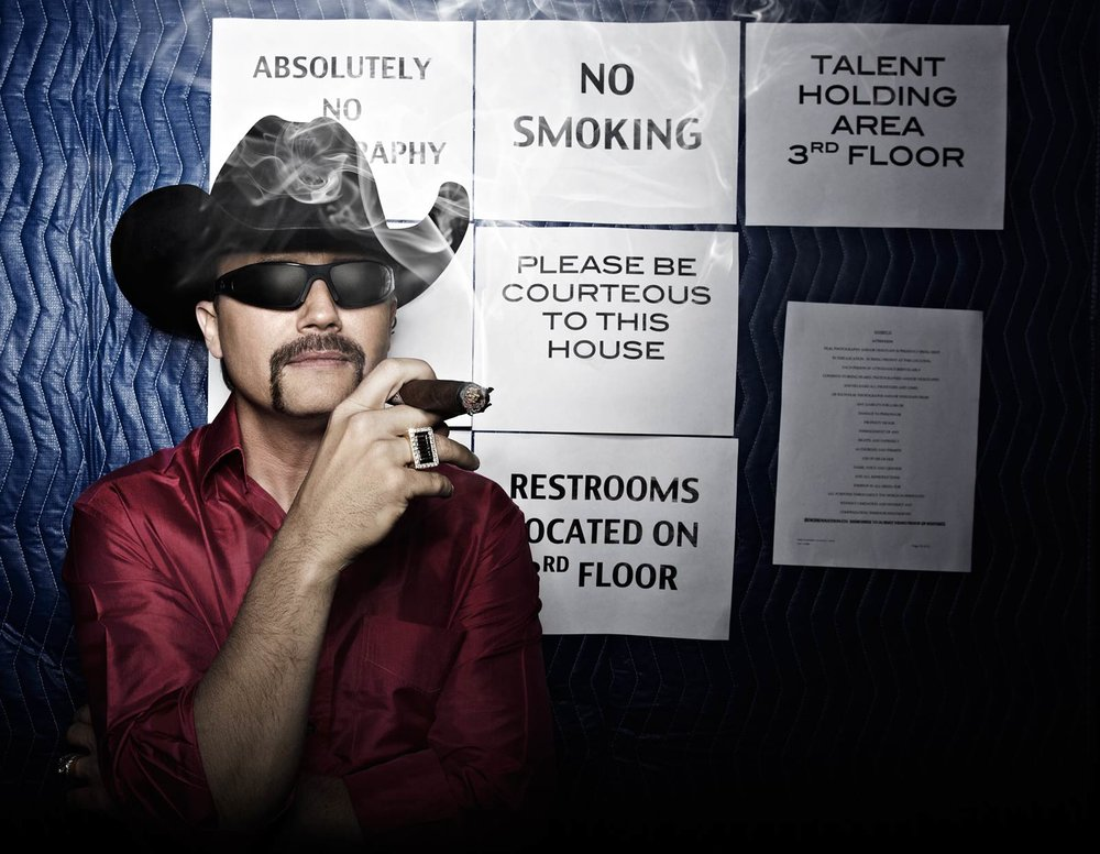 Mark DeLong - Celebrity Photographer - Musician from Big and Rich smokes a cigar in front of a no smoking sign.