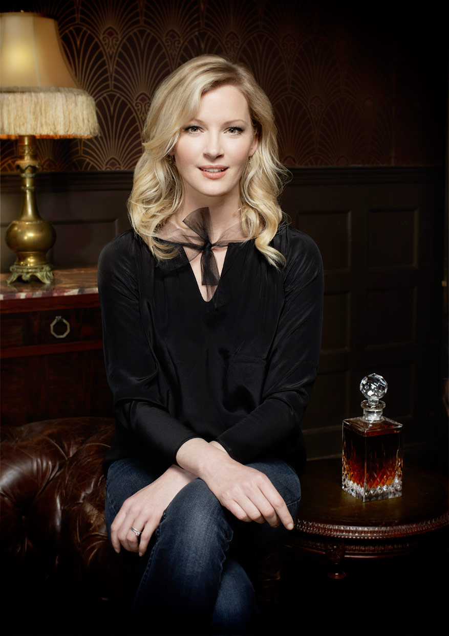 Mark DeLong - Celebrity Photographer - Blonde actress in a black top sitting next to a bottle of alcohol.