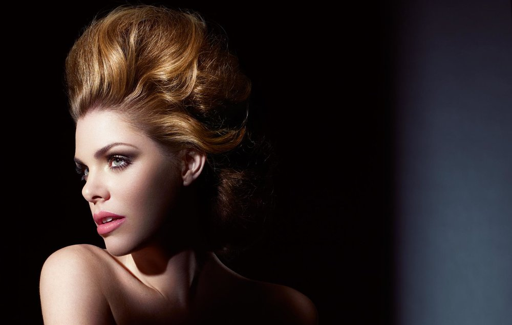 Mark DeLong - Beauty Photographer - Portrait of woman with strawberry blond hair in a dark room looking to the side