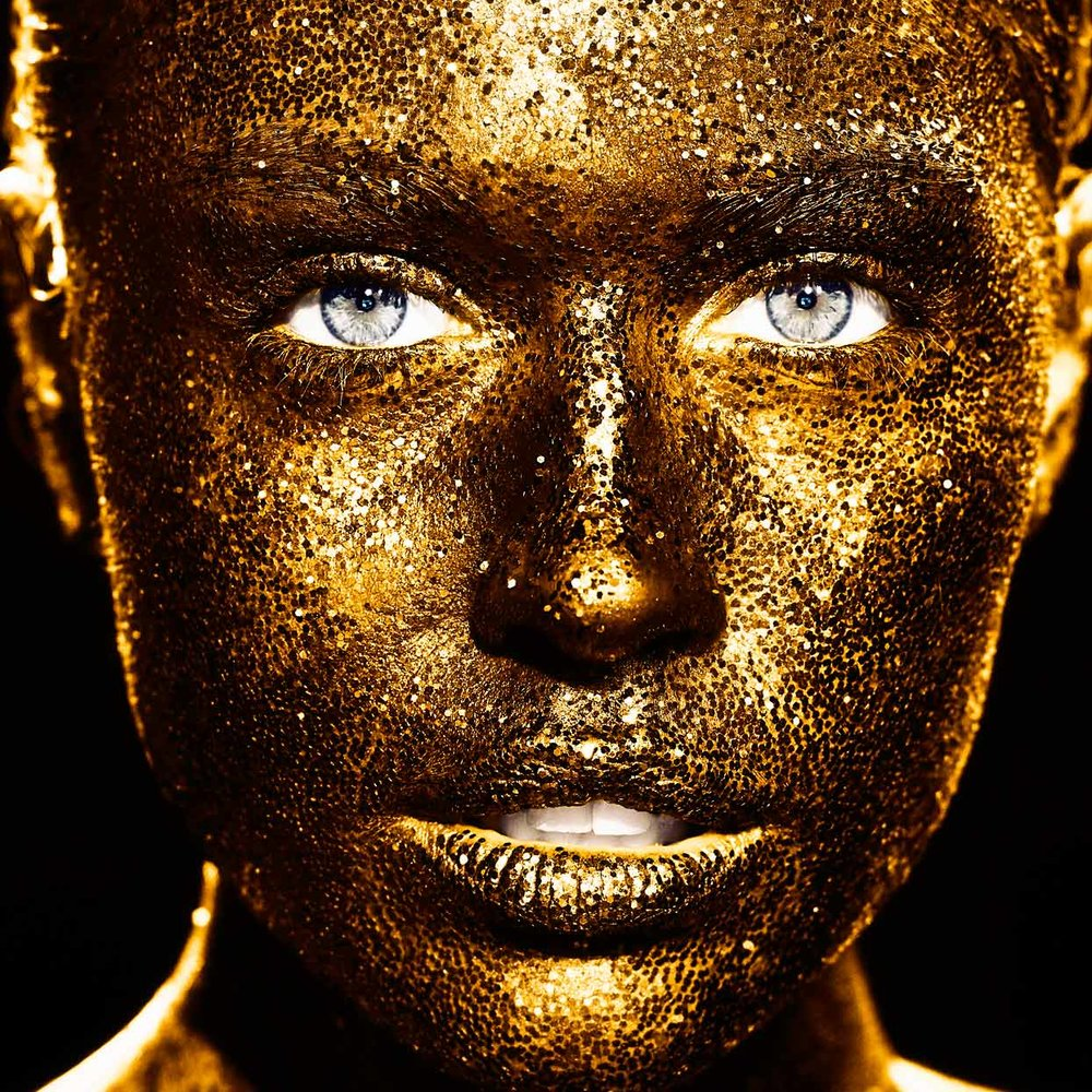 Mark DeLong - Beauty Photographer - Face of woman covered in gold glitter skin with gray eyes