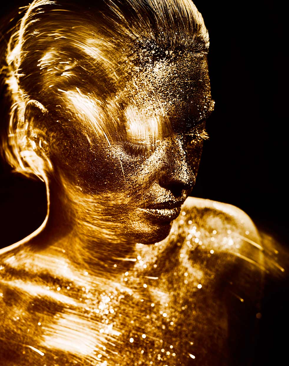 Mark DeLong - Beauty Photographer - Motion streaks of woman covered in gold glitter skin