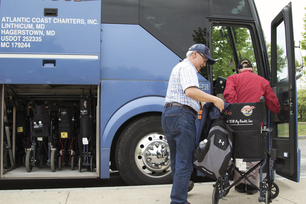 A volunteer helps a veteran with the Central Valley Honor Flight program return to the tour bus after viewing the National World War II Memorial in Washington, D.C., on April 26, 2016. Sixty-six veterans, 63 men and three women, from the central San Joaquin Valley in California flew to the nation's capital as part of the Central Valley Honor Flight program.