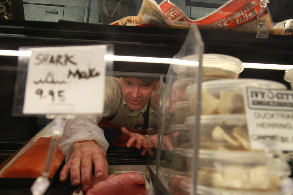 Fishmonger Peter Martone is arranging the display of seafood in Ivy City Smokehouse in Washington, D.C., on Dec. 7, 2016. Martone has experience in purchasing, handling and selling seafood for more than 30 years.