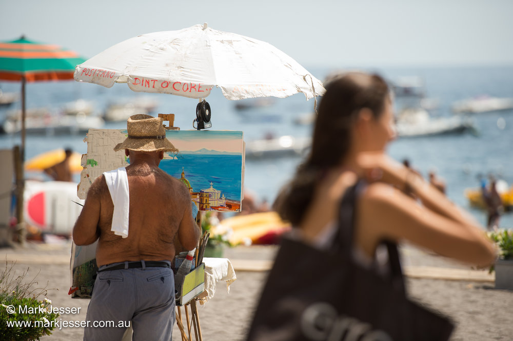 (Photo Mark Jesser) Positano, Italy. - Artist paints in the sun, girls tan.