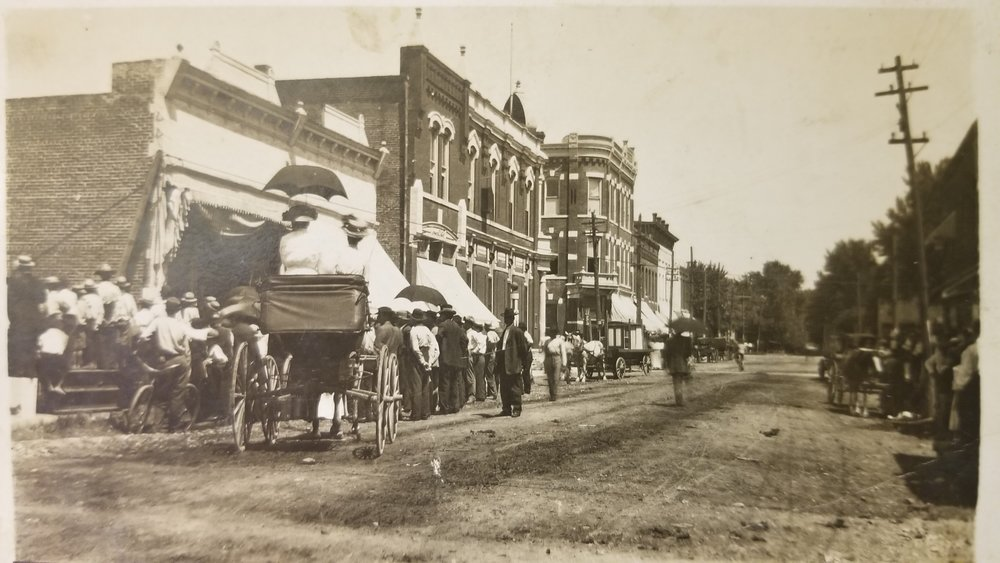 This photo is from a few years after the robbery. Starting on the left, the first building would have been the Bentonville Sun office, next is Kit Campbell's Barbershop, and finally the bank on the corner.
