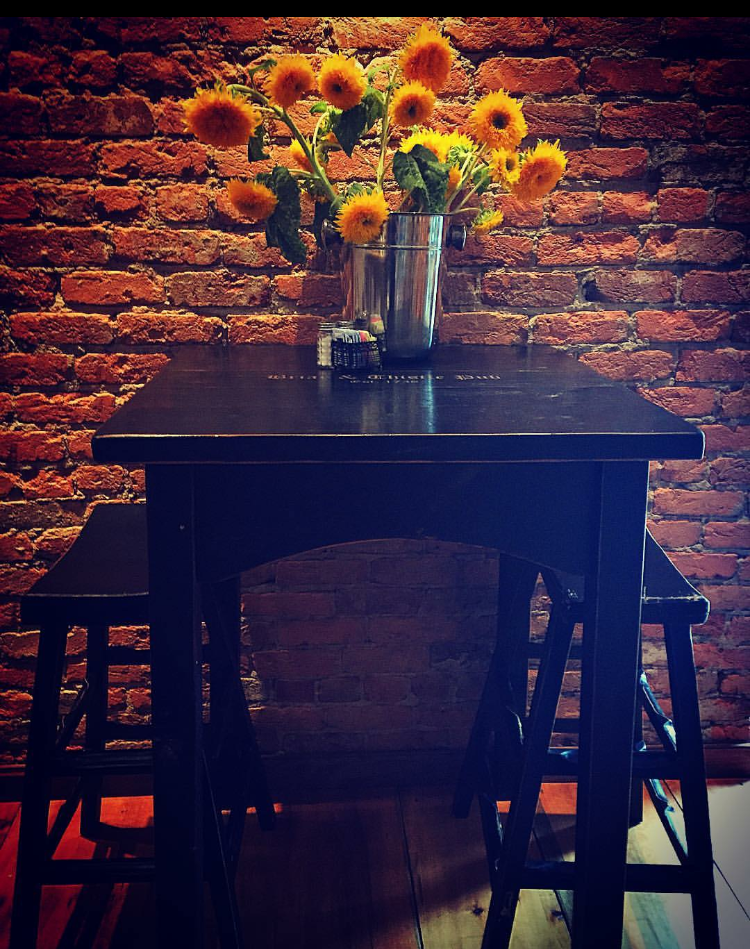 Your bar table awaits in Tula's beautiful brick and wood bar . . .