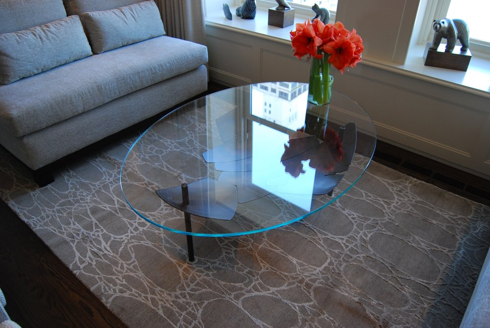 Custom fabricated metal and glass table. Recovered furniture and custom rug. Palmolive Building.