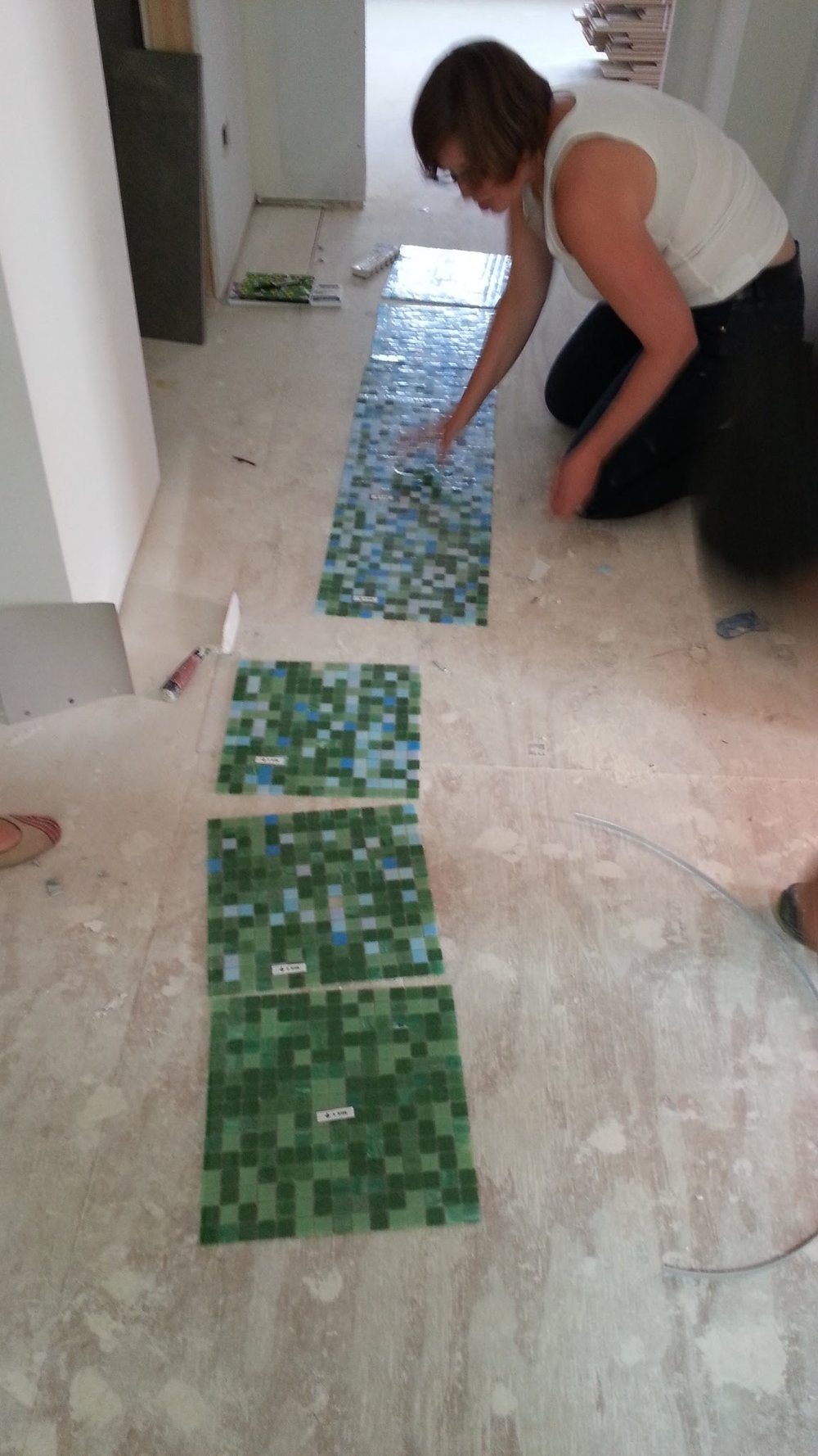 Claudia laying out the hall bathroom wall tile pattern.